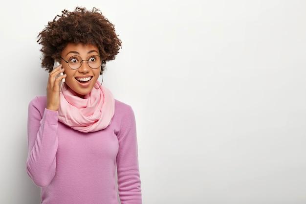 Wesoła młoda dama dzwoni do kogoś przez nowoczesny telefon komórkowy, wykorzystuje nowoczesne technologie do komunikacji
