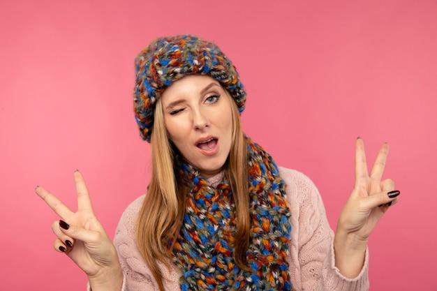 Wesoła młoda dama mruga i pokazuje znak pokoju w czapce zimowej w różowym studio.