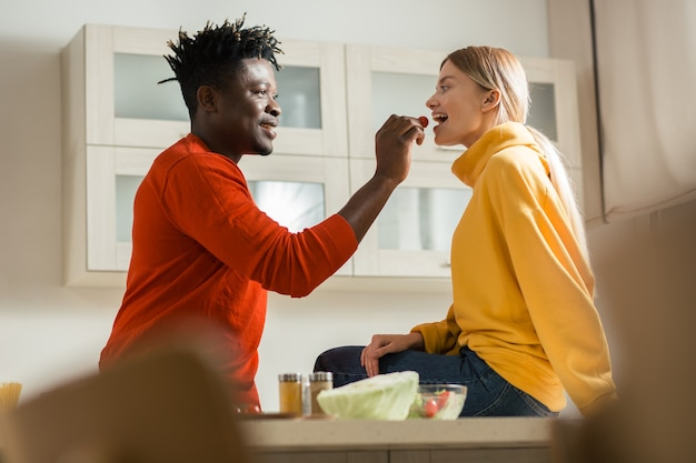 Wesoła młoda dama siedzi na kuchennym stole i uśmiecha się, podczas gdy szczęśliwy chłopak karmi ją pomidorkami cherry