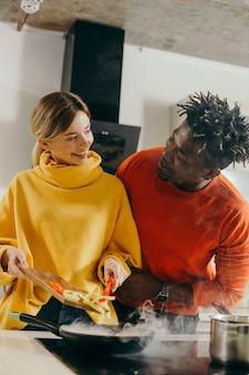 Wesoła młoda dama stoi w kuchni i uśmiecha się do swojego pozytywnego chłopaka, kładąc na patelnię warzywa z deski do krojenia