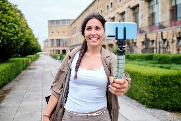 Wesoła młoda dorosła kobieta prowadzi wideorozmowę na zewnątrz, trzymając smartfon na statywie i rozmawiając z kamerą