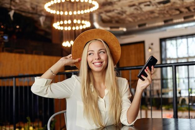 Wesoła młoda, dość długowłosa kobieta patrzy na bok z uroczym uśmiechem i trzyma rękę na kapeluszu, trzymając telefon komórkowy podczas pozowania nad miejską kawiarnią