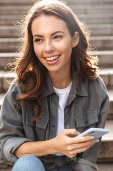 Wesoła młoda dziewczyna siedzi na schodach na zewnątrz, używając telefonu komórkowego