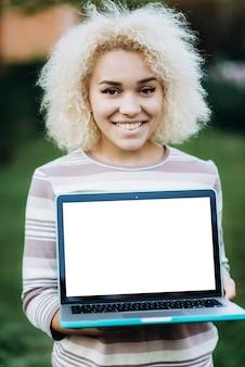 Wesoła młoda dziewczyna student posiada laptop z białym ekranie