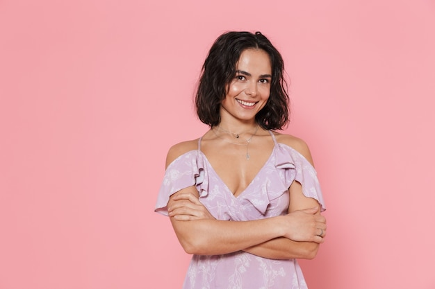 Wesoła młoda dziewczyna ubrana w letnią sukienkę stojącą na białym tle nad różową ścianą, z założonymi rękoma