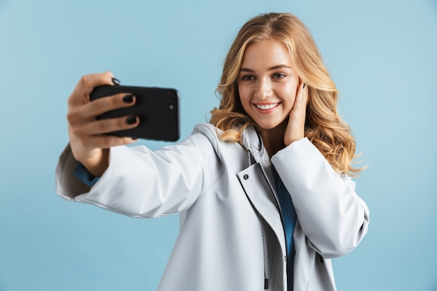 Wesoła młoda dziewczyna ubrana w płaszcz przeciwdeszczowy stojący na białym tle, biorąc selfie