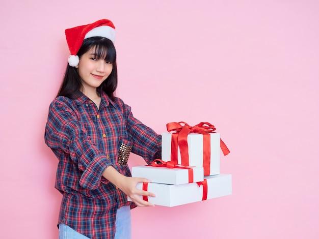 Wesoła młoda dziewczyna ubrana w santa hat dając pudełka na białym tle nad różowym, miejsca na tekst