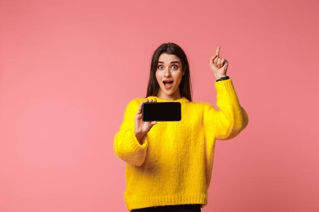 Wesoła młoda dziewczyna ubrana w sweter stojący na białym tle nad różowym, pokazując pusty ekran telefonu komórkowego