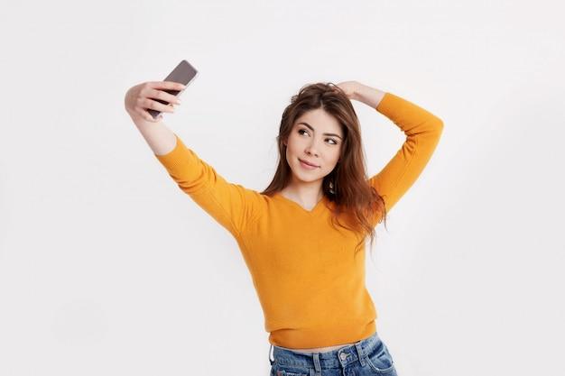 Wesoła młoda dziewczyna w pomarańczowym swetrze robi zdjęcie selfie na swoim telefonie. stylowa brunetka na jasnym tle z miejsca na tekst