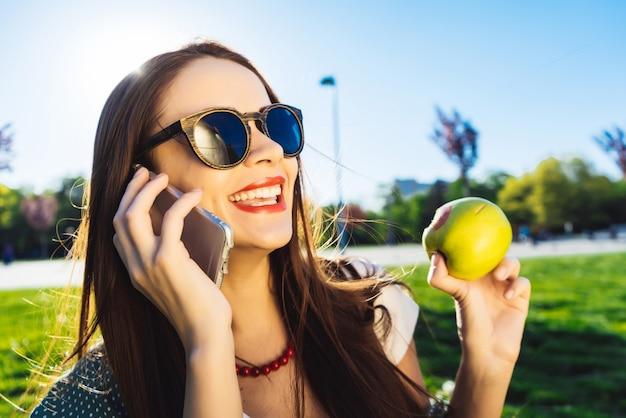 Wesoła młoda dziewczyna z długimi włosami siedzi na trawniku w parku, je zielone jabłko, rozmawia przez telefon