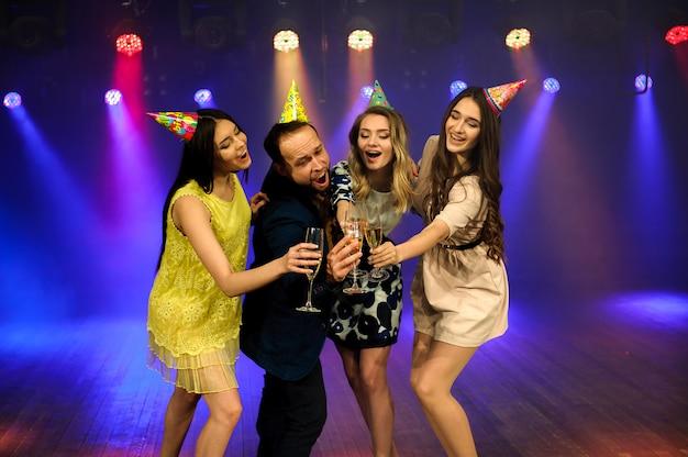 Wesoła młoda firma świętuje urodziny w nocnym klubie.