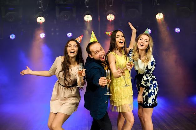 Wesoła młoda firma świętuje urodziny w nocnym klubie