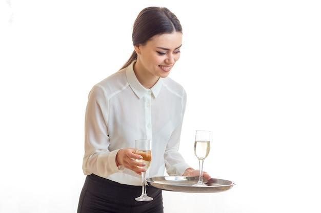 Wesoła młoda kelnerka z kieliszkami wina na trey uśmiechach na białym tle