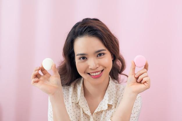 Wesoła młoda kobieta azjatyckich trzyma dwa macarons przed oczami na różowej ścianie.