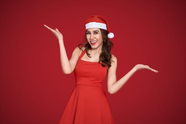 Wesoła młoda kobieta azji w czerwonej sukience santa z gestem otwartej dłoni.