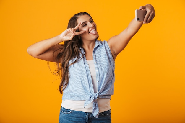 Wesoła młoda kobieta, biorąc selfie z wyciągniętą ręką