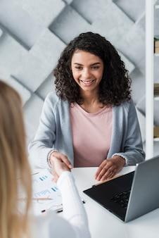 Wesoła młoda kobieta brunetka drżenie rąk z kolegą siedzi w biurze