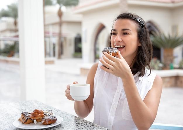 Wesoła młoda kobieta, ciesząc się poranną kawą z pączkami na odkrytym tarasie