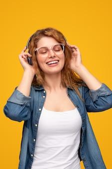 Wesoła młoda kobieta ciesząca się muzyką w słuchawkach