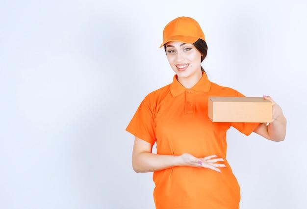 Wesoła młoda kobieta dostawy trzymająca pakiet ręką na białej ścianie