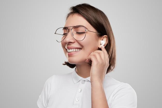 Wesoła młoda kobieta dostosowująca słuchawki tws