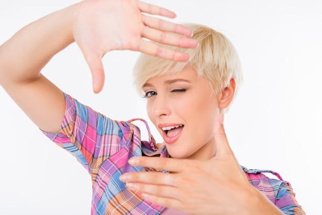 Wesoła młoda kobieta gestykuluje ramkę palca i uśmiecha się