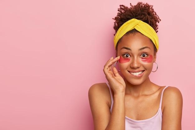 Wesoła młoda kobieta gryzie usta, ma szczęśliwy wyraz twarzy, zdrową skórę twarzy, nosi plastry pod oczami w celu zmniejszenia worków, ma zabiegi przeciwzmarszczkowe