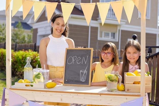 Wesoła młoda kobieta i mała dziewczynka trzyma małą tablicę z obrazem napoju i otwarte ogłoszenie, stojąc przy straganie