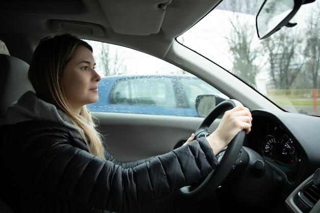 Wesoła młoda kobieta jazdy samochodem, zdjęcie wewnątrz samochodu. deszczowy dzień, styl życia