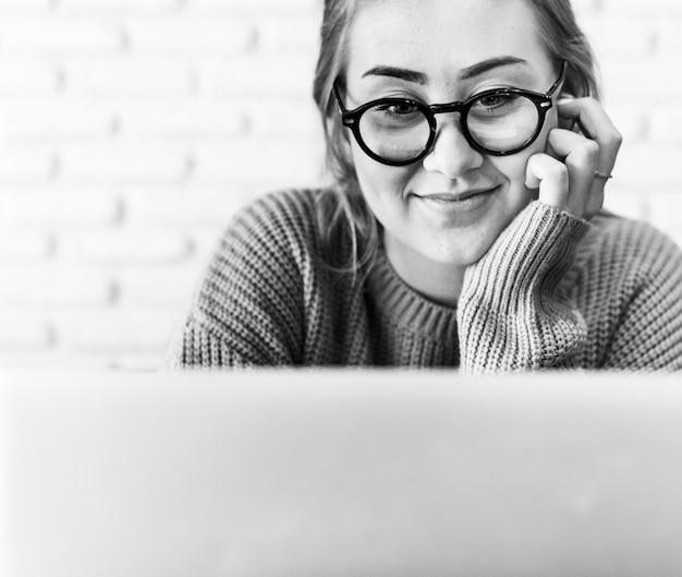 Wesoła młoda kobieta korzysta z laptopa