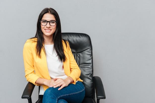 Wesoła młoda kobieta nosi okulary i ubrana w żółtą kurtkę, siedząc na krześle biurowym na szarej powierzchni.