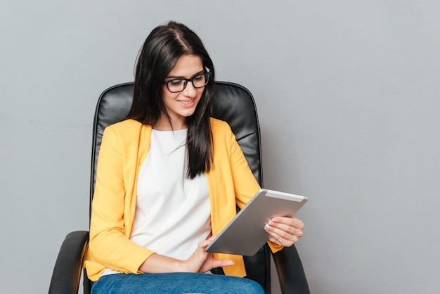 Wesoła młoda kobieta nosi okulary i ubrana w żółtą kurtkę, siedząc na krześle biurowym podczas korzystania z komputera typu tablet na szarej powierzchni.