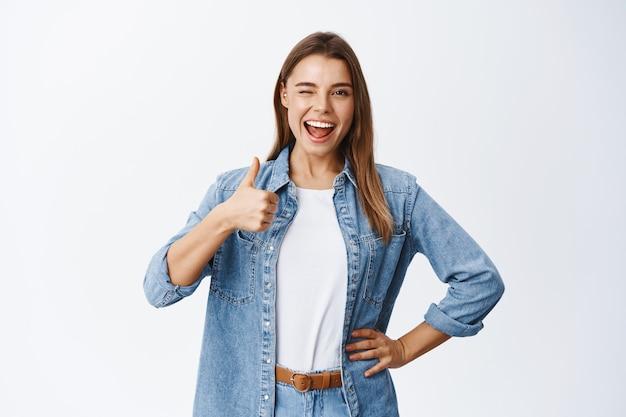 Wesoła młoda kobieta o blond włosach i swobodnym ubraniu, pokazująca kciuk w górę z aprobatą, lubi dobrą rzecz, pochwalać i polecać, chwalić dobrą robotę lub mówić tak, biała ściana
