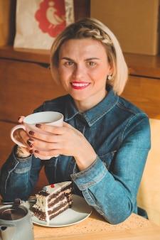 Wesoła młoda kobieta picia ciepłej kawy lub herbaty, ciesząc się nim siedząc w kawiarni. atrakcyjna kobieta trzyma filiżankę kawy .. rozgrzewający napój.