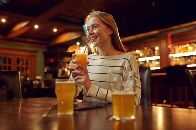 Wesoła młoda kobieta pije koktajl w barze. grupa ludzi wypoczywa w pubie, nocne życie, przyjaciele świętują wydarzenie w restauracji