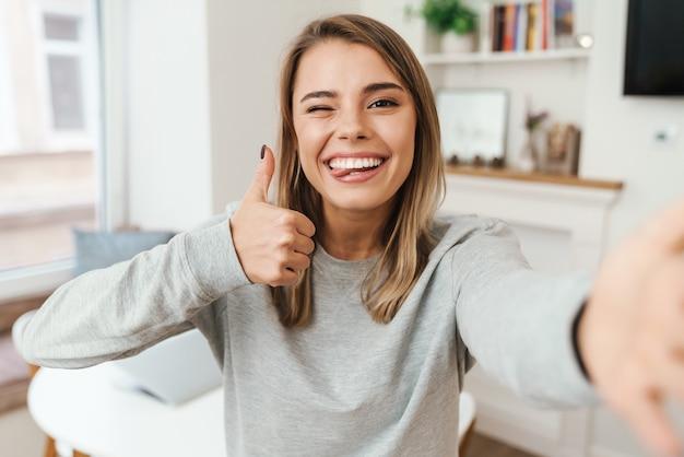 Wesoła młoda kobieta pokazując kciuk do góry i mrugając podczas robienia selfie w salonie