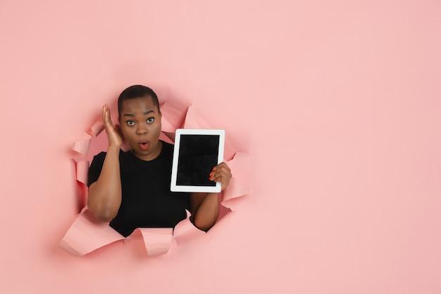 Wesoła młoda kobieta pozuje w dziurze z rozdartego koralowego papieru