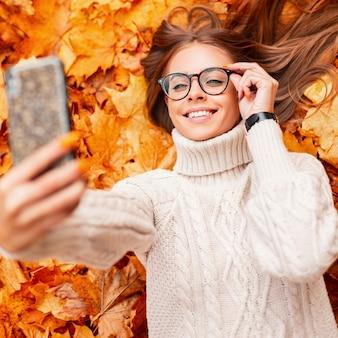 Wesoła młoda kobieta prostuje modne okulary i robi selfie na nowoczesnym smartfonie. zabawna śliczna hipster dziewczyna w swetrze z dzianiny leży na żółto-pomarańczowych liściach w parku. widok z góry