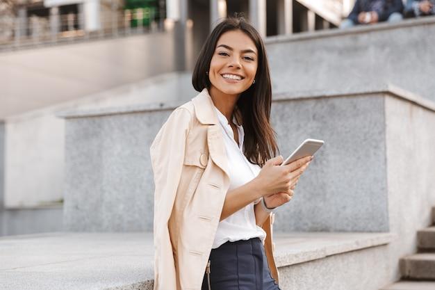 Wesoła młoda kobieta przy użyciu telefonu komórkowego