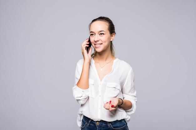 Wesoła młoda kobieta rozmawia przez telefon komórkowy na białym tle na szarej ścianie