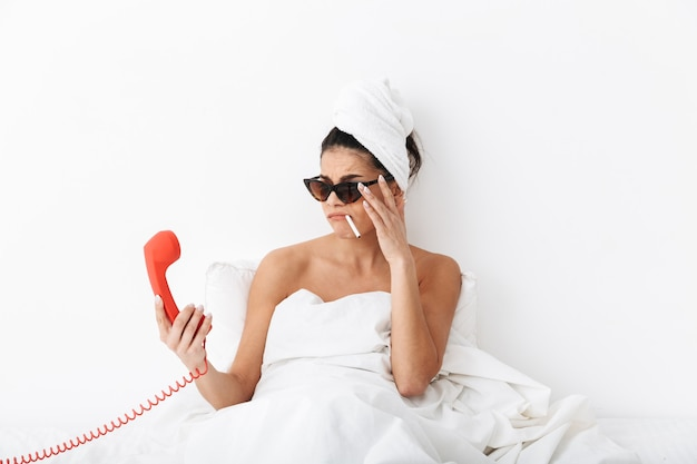 Wesoła młoda kobieta siedzi w łóżku po prysznicu owinięta w koc, nosi okulary przeciwsłoneczne, pali, rozmawia przez telefon stacjonarny