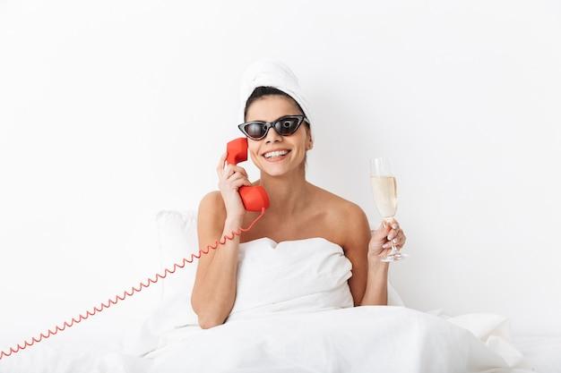 Wesoła młoda kobieta siedzi w łóżku po prysznicu owinięta w koc, nosi okulary przeciwsłoneczne, rozmawia przez telefon stacjonarny, trzymając kieliszek szampana