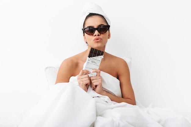 Wesoła młoda kobieta siedzi w łóżku po prysznicu owinięta w koc, nosząca okulary przeciwsłoneczne i jedząca czekoladę