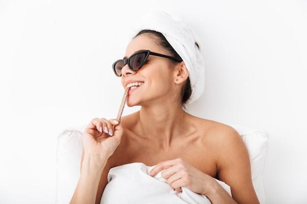 Wesoła młoda kobieta siedzi w łóżku po prysznicu owinięta w koc, nosząca okulary przeciwsłoneczne, jedząca cukierki