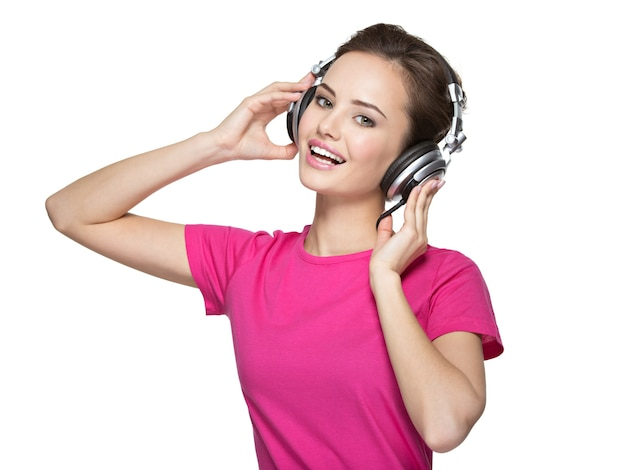 Wesoła młoda kobieta słuchania muzyki w słuchawkach