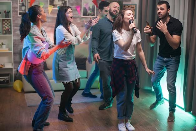 Wesoła młoda kobieta śpiewa na mikrofonie, podczas gdy jej przyjaciele tańczą na imprezie.