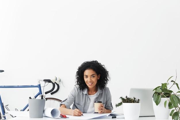 Wesoła młoda kobieta stażysta trzymając papierowy kubek kawy na wynos podczas pracy
