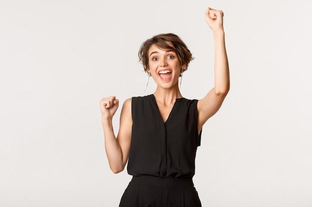 Wesoła młoda kobieta świętuje sukces, triumfuje i robi gest pompy pięści, osiągnąć cel nad białymi.