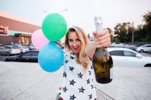 Wesoła młoda kobieta trzyma butelkę szampana i balony na zewnątrz