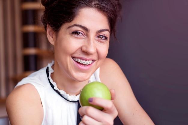 Wesoła młoda kobieta trzyma jabłko